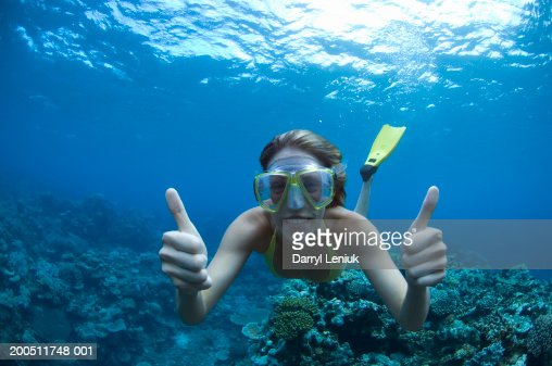 Fiji, young woman snorkeling, giving thumbs up, underwater view : Stock Photo