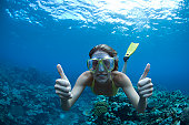 Fiji, young woman snorkeling, giving thumbs up, underwater view