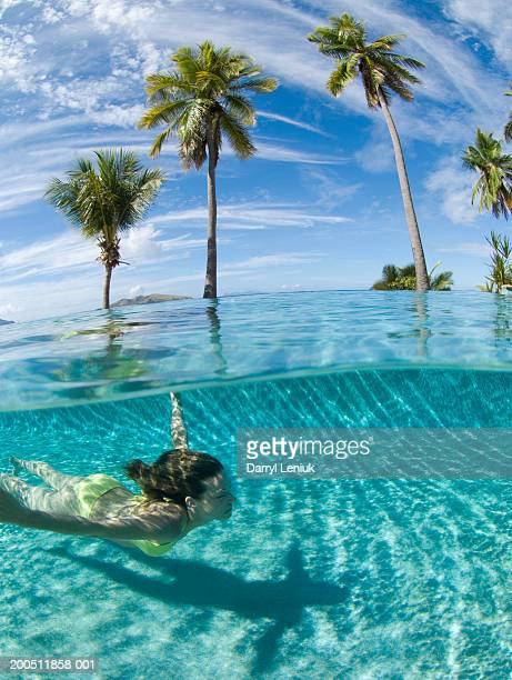 Fiji, young woman swimming in pool, surface view