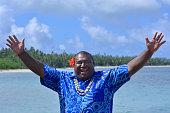 "Fijian man greeting in Fijian language ""Bula"", (general greeting hello) against The Blue Lagoon on Nanuya Lailai Island on of the Yasawa Islands of Fiji. Real people copy space"