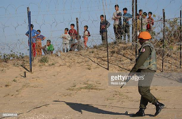 Fijian soldier of the Multinational Peackeeping Force and Observers patrols the perimiter fence at camp One Bravo watched by beduin children as New...