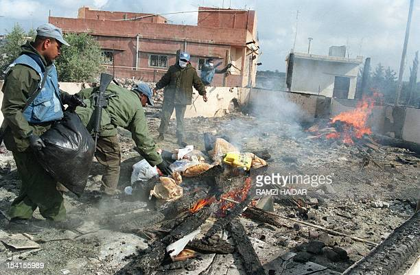 Fijian UN soldiers colllect and burn 19 April 1996 in Qana the belongings of dead Lebanese refugees burned in the shelling of the United Nations...