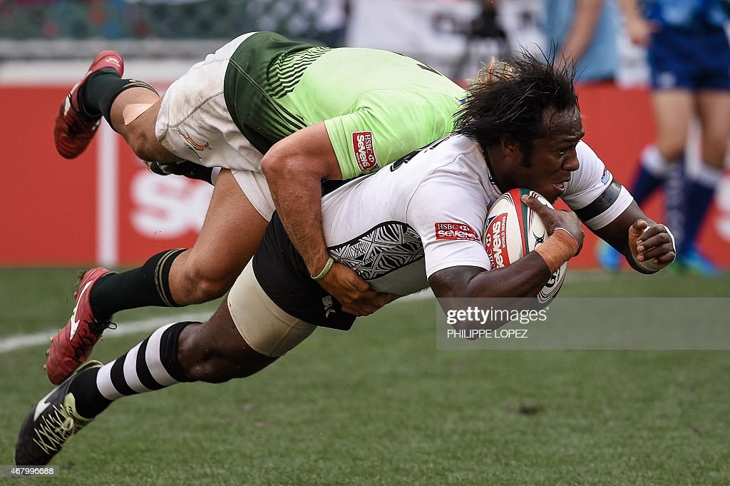 Fiji's Pio Tuwai scores a try as South Africa's Werner Kok tackles him during a semifinal match between Fiji and South Africa on the third and final...