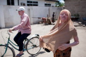 Fikiri Sultan a member of Tanzania's Albino United football club rides on his bicycle past his sister Fatuma Sultan getting ready for work in Dar es...