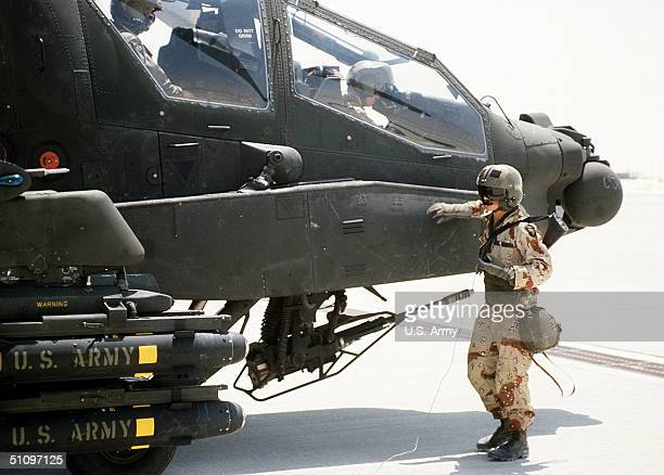 A Helicopter Crewman Stands Beside An Ah64A Apache Helicopter As It Is Prepared For Takeoff During Operation Desert Shield January 23 1991 The...
