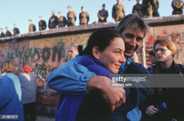 A West German Couple Embraces In Front Of The Berlin Wall Prior To It Being Lifted During The Collapse Of Communism In East Berlin On November 10...
