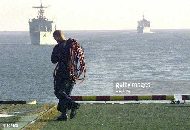 Cpl John D Goekler From Redding Ca Assigned To The 31St Marine Expeditionary Unit Hauls A CompressedAir Hose Toward A Av8B 'Harrier' On Board The...