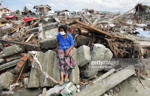 File photo dated 11 January 2005 shows an Acehnese woman at the ruins of her home in downtown Banda Aceh a month after a powerful tsunami hit the...