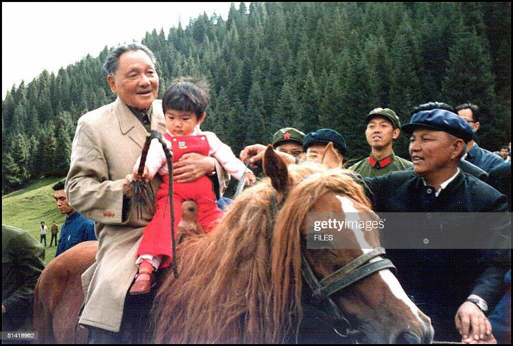 File photo dated in 1981 shows senior Chinese leader Deng Xiaoping riding a horse with one of his granddaughters during a visit to Xinjiang China...