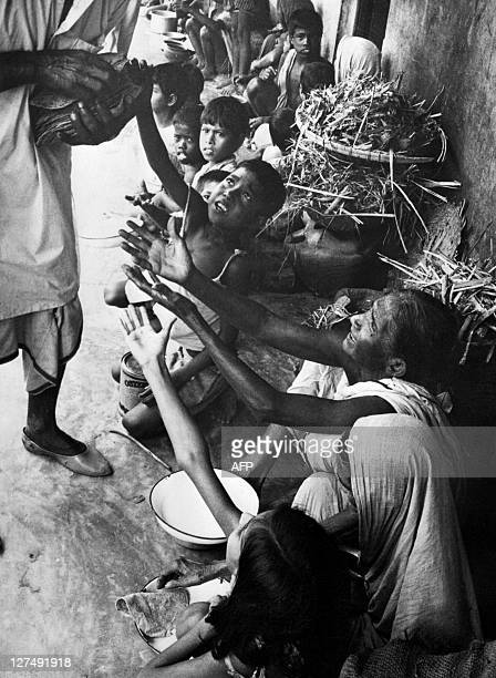 File photo dated September 1974 shows flood victims near Dhaka Bangladesh reaching out for relief food distribution In the early 1970s Bangladesh...