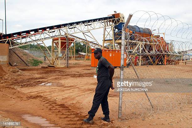 A file photo taken on December 14 2011 shows a private security employee guarding a diamond processing plant in the diamondrich eastern Marange...