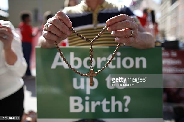 A file photo taken on July 10 2013 shows a protester holding rosary beads and holding an antiabortion placard in front of the gates of the Irish...