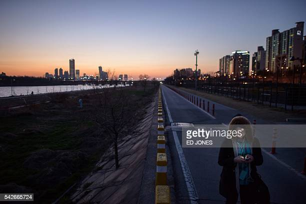 A file photo taken on March 31 2014 shows a woman checking a smartphone as she walks along the Han river in Seoul Tired of endless text messages from...