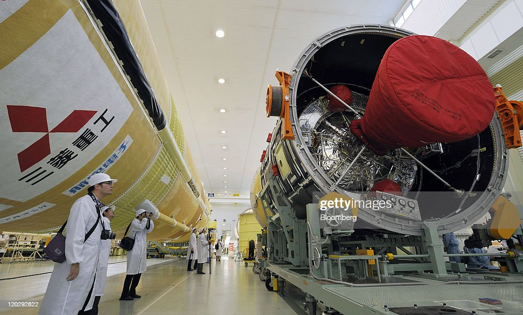 A file photograph shows members of the media looking at a HIIB rocket manufactured by Mitsubishi Heavy Industries Ltd at the company's Nagoya...