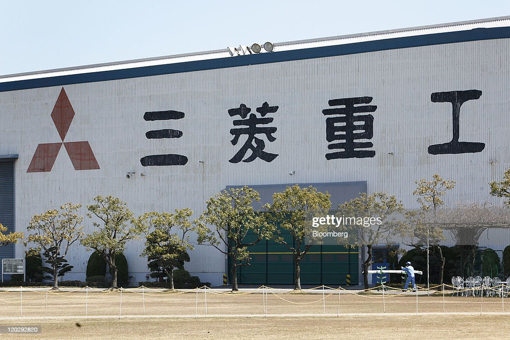 A file photograph shows Mitsubishi Heavy Industries Ltd. employees working in front of the company's Nagoya Aerospace Systems Works Tobishima Plant in Tobishima Village, Aichi Prefecture, Japan, on Tuesday, April 5, 2011. Hitachi Ltd. and Mitsubishi Heavy Industries Ltd. agreed to discuss a combination of some businesses including nuclear power plants and railway systems, a person familiar with the matter said. Photographer: Kiyoshi Ota /Bloomberg via Getty Images
