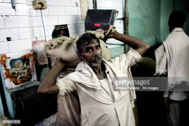File picture a man lifts a bag full of spices of the scales in the old spice market old Delhi India