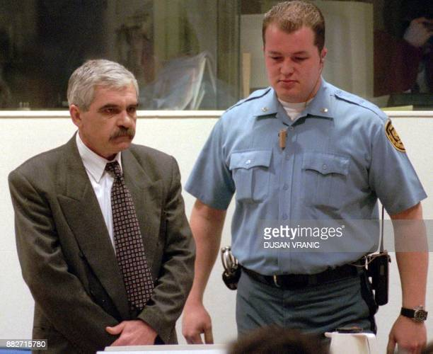 File picture dated 19 January 1998 of Croatian Serb Slavko Dokmanovic flanked by a UN security guard as he stands trial before the United Nations War...