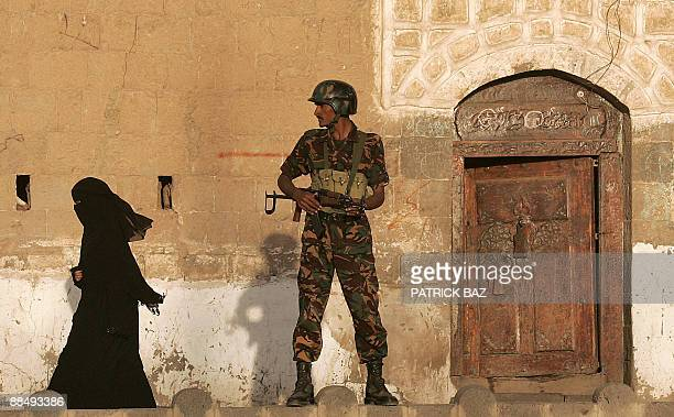 File picture dated March 1 2006 shows a Yemeni woman walking past a guard standing in front of a traditional building in Sanaa's Old City Seven out...