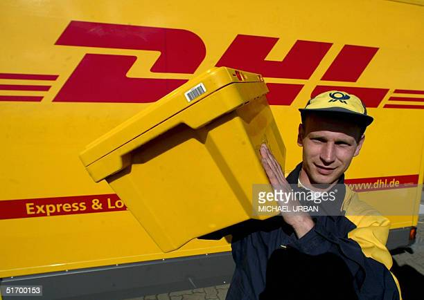 A file picture taken 02 April 2003 shows an employee of Deutsche Post carrying a box past a transporter of the company's courier service DHL in...