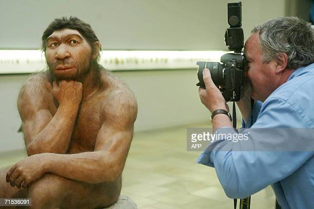 STORY File picture taken 28 July 2004 shows a photographer taking pictures of the Neanderthal man ancestor's reconstruction displayed in a show of...