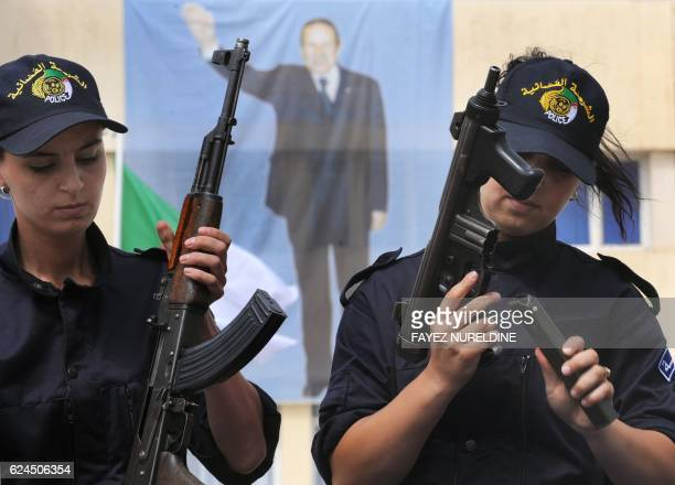 A file picture taken on August 6 shows newly graduated Algerian police women showing their skills in front of President Abdelaziz Bouteflika's poster...