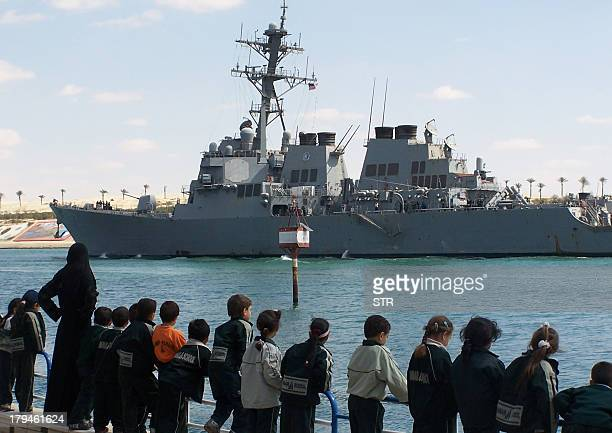 A file picture taken on March 16 shows Egyptians watching guided missile destroyer USS Mahan crossing the Suez Canal near Egypt's port city of...