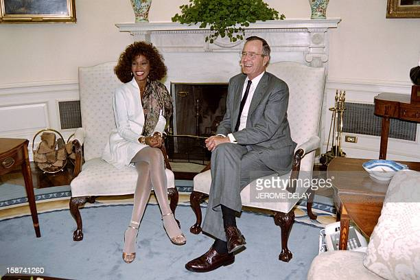 A file picture taken on May 2 19904 in Washington shows US singer Whitney Houston posing with then US President George Bush at the White House...