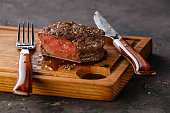 Filet Mignon Steak on wooden board on black background