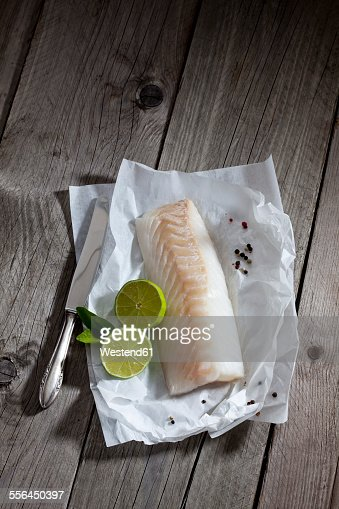 Filet of codfisch, lime and knife, and peppercorns on greaseproof paper on wood