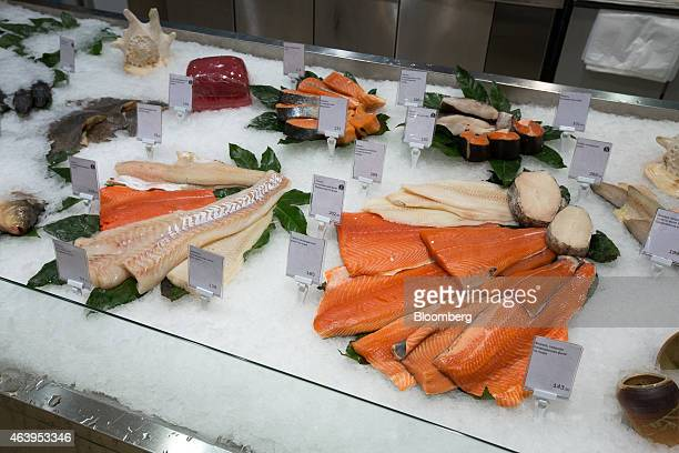 Filets of fresh fish including salmon right sit on display at the fishmonger's counter of an Azbuka Vkusa OOO which translates as 'Elements of Taste'...