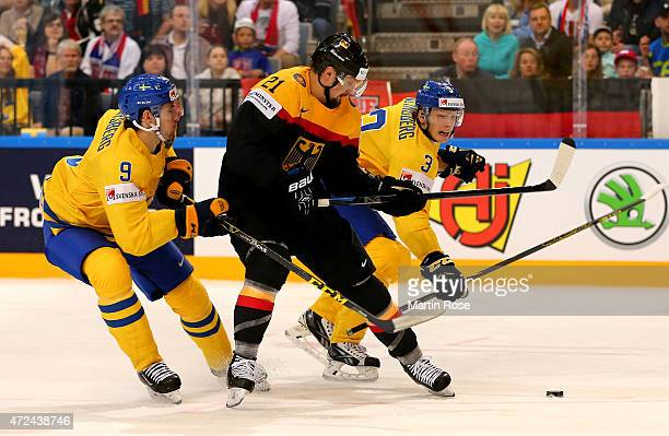 Filip Forsberg and John Klingberg of Sweden and Nicolas Kramer of Germany battle for the puck during the IIHF World Championship group A match...