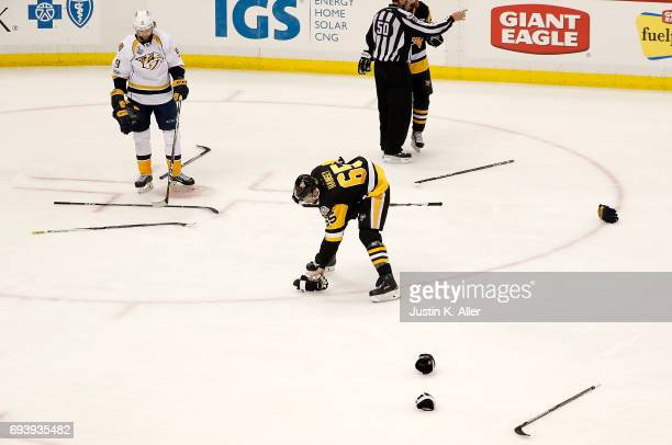 Filip Forsberg of the Nashville Predators and Ron Hainsey of the Pittsburgh Penguins puck up gloves and stick in the third period in Game Five of the...