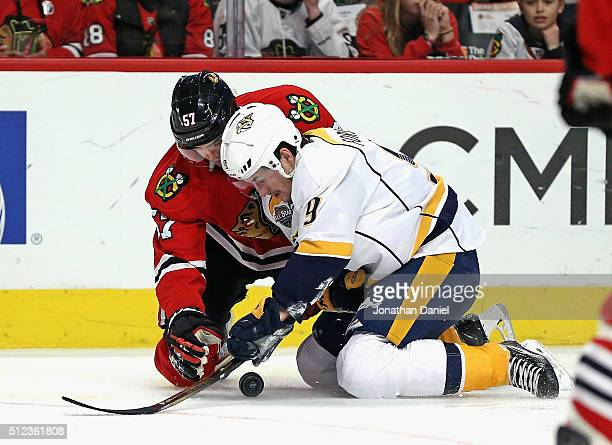 Filip Forsberg of the Nashville Predators and Trevor van Riemsdyk of the Chicago Blackhawks battle for the puck on their knees at the United Center...