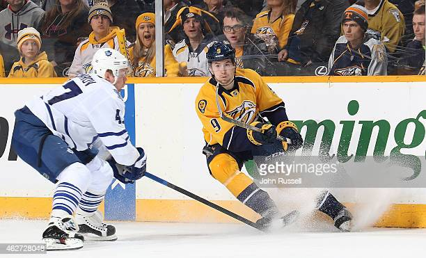 Filip Forsberg of the Nashville Predators centers the puck against Leo Komarov of the Toronto Maple Leafs during an NHL game at Bridgestone Arena on...