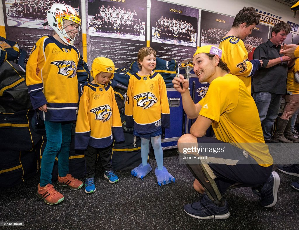 Filip Forsberg #9 of the Nashville Predators meets with cancer survivors after a 6-3 win against the Washington Capitals on Hockey Fights Cancer Night at Bridgestone Arena on November 14, 2017 in Nashville, Tennessee.