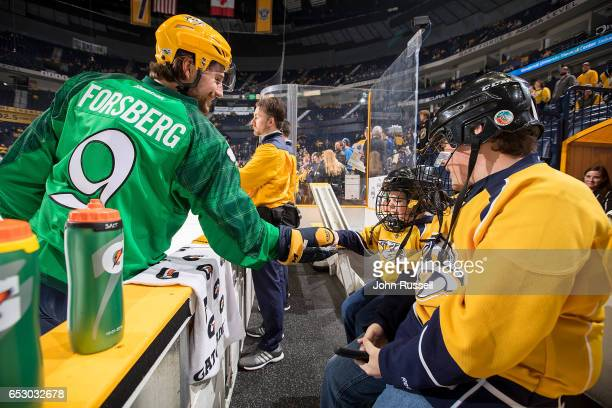 Filip Forsberg of the Nashville Predators offers a puck to a young fan during warmups prior to an NHL game against the Winnipeg Jets at Bridgestone...
