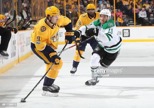 Filip Forsberg of the Nashville Predators passes the puck against Mattias Janmark of the Dallas Stars during an NHL game at Bridgestone Arena on...