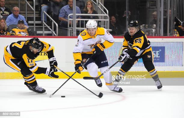 Filip Forsberg of the Nashville Predators skates with the puck against Sidney Crosby and Jake Guentzel of the Pittsburgh Penguins at PPG PAINTS Arena...