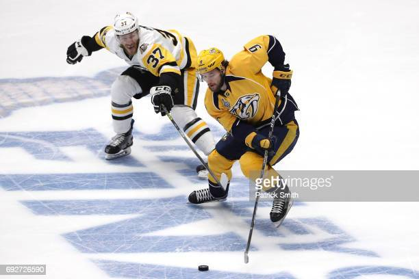 Filip Forsberg of the Nashville Predators skates with the puck against Carter Rowney of the Pittsburgh Penguins during the first period in Game Four...