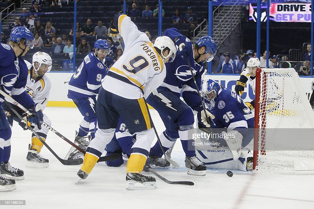 <a gi-track='captionPersonalityLinkClicked' href=/galleries/search?phrase=Filip+Forsberg&family=editorial&specificpeople=8768623 ng-click='$event.stopPropagation()'>Filip Forsberg</a> #9 of the Nashville Predators takes a shot against goaltender Riku Helenius #35 and <a gi-track='captionPersonalityLinkClicked' href=/galleries/search?phrase=Victor+Hedman&family=editorial&specificpeople=4784238 ng-click='$event.stopPropagation()'>Victor Hedman</a> #77 of the Tampa Bay Lightning during the first period at Tampa Bay Times Forum on September 19, 2013 in Tampa, Florida.