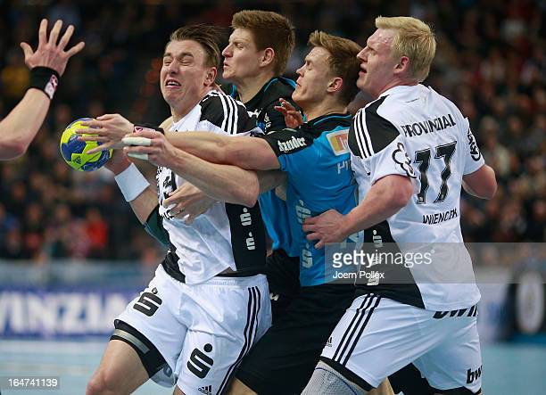 Filip Jicha of Kiel is challenged by Toon Leenders and Niclas Pieczkowski of Essen during the DKB Handball Bundesliga match between THW Kiel and...