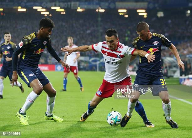 Filip Kostic of Hamburg is challenged by Bernardo and Diego Demme of Leipzig during the Bundesliga match between Hamburger SV and RB Leipzig at...
