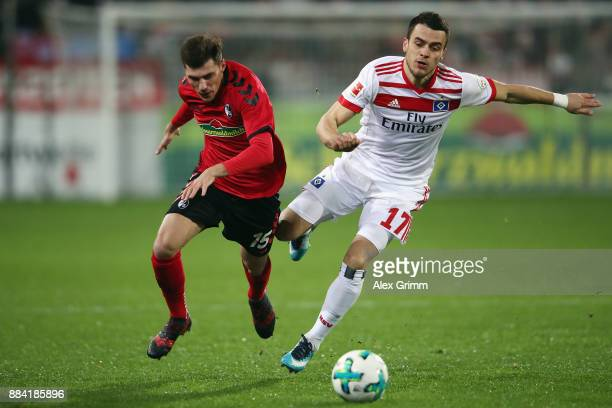 Filip Kostic of Hamburg is challenged by Pascal Stenzel of Freiburg during the Bundesliga match between SportClub Freiburg and Hamburger SV at...