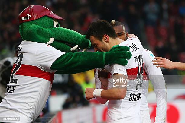 Filip Kostic of Stuttgart celebrates his team's fourth goal with with team mate Serey Die and mascot Fritzle during the Bundesliga match between VfB...