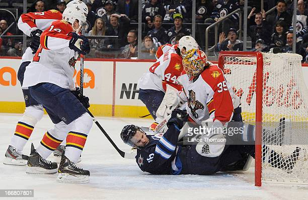Filip Kuba and Tomas Fleischmann of the Florida Panthers look on as Andrew Ladd of the Winnipeg Jets slides into goaltender Jacob Markstrom during...