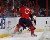 Filip Kuba of the Florida Panthers checks David Clarkson of the New Jersey Devils off the puck at the BBT Center on March 30 2013 in Sunrise Florida