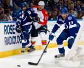 Filip Kuba of the Florida Panthers checks Tom Pyatt of the Tampa Bay Lightning as teammate Alex Killorn moves the puck during the first period of the...