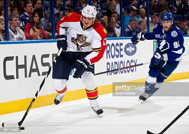 Filip Kuba of the Florida Panthers controls the puck around the net trailed by Steven Stamkos of the Tampa Bay Lightning during the first period of...