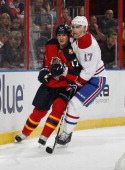 Filip Kuba of the Florida Panthers defends against Rene Bourque of the Montreal Canadiens behind the net during second period action at the BBT...