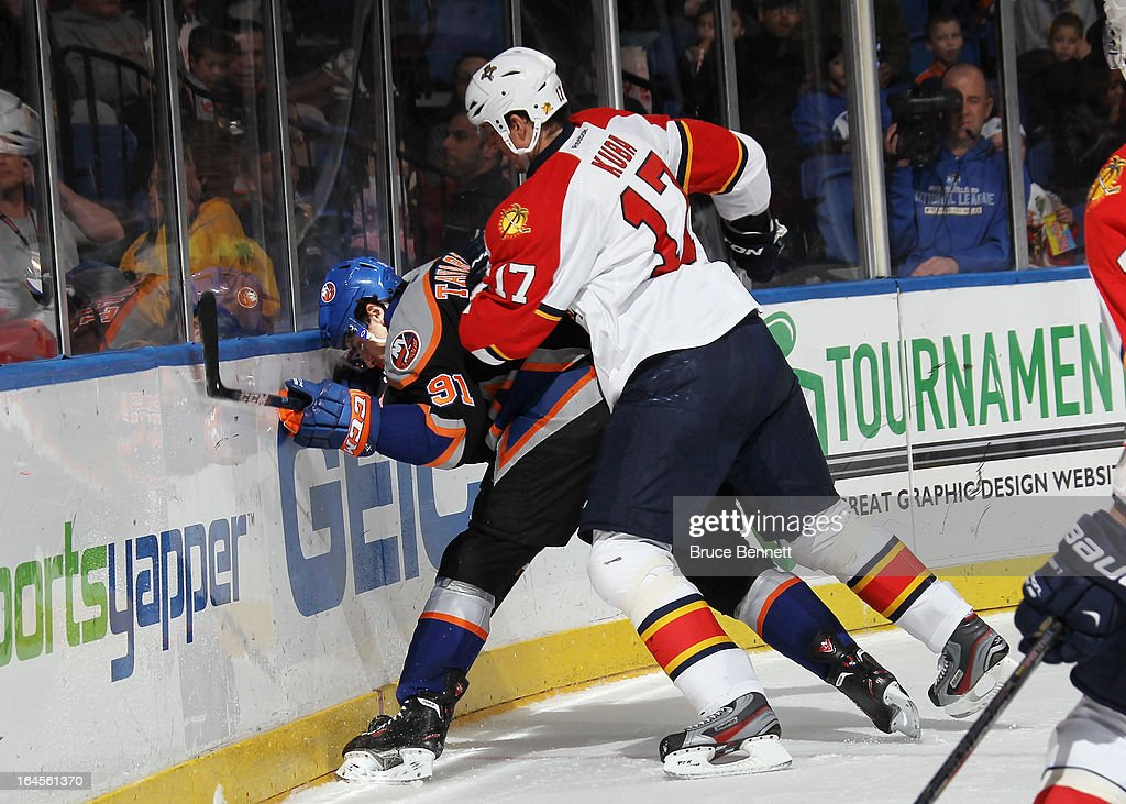 Filip Kuba #17 of the Florida Panthers hits John Tavares #91 of the New York Islanders into the boards at the Nassau Veterans Memorial Coliseum on March 24, 2013 in Uniondale, New York.